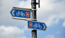 Two bicycle signs pointing in different directions